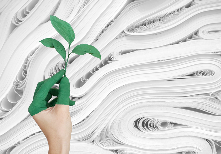 A hand with green painted fingers holds a small plant against a background of paper rolls
