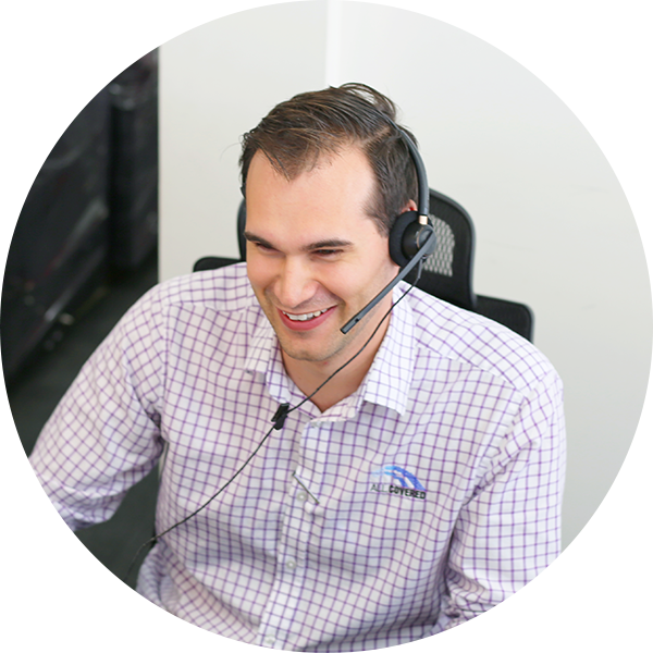 IT Tech wearing headset smiles at desk
