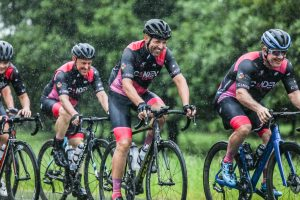 Cyclists riding in the rain with green vegetation in background