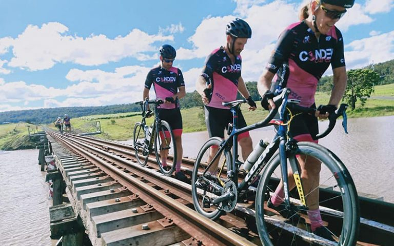 Three cyclists walk across train track above flooded highway