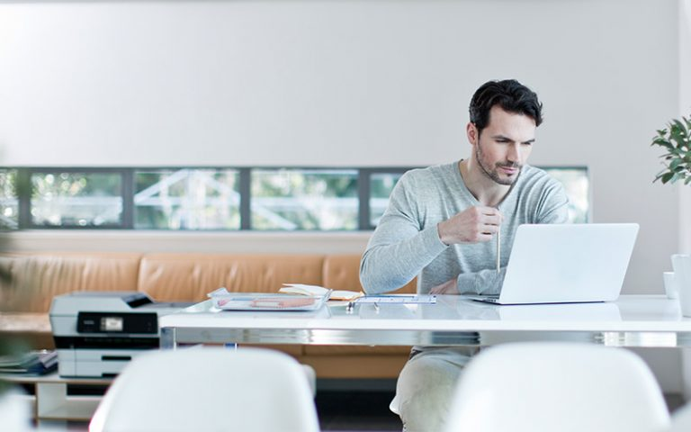 Man sits at desk with Brother printer in background